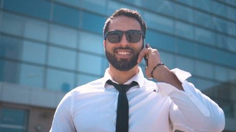 Dubai businessman in sunglasses on mobile phone