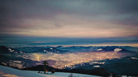 Dusk from the top of a snowy and cloudy mountain range