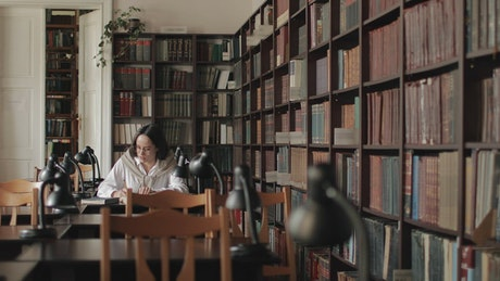 Educated woman studies for exam in university  library