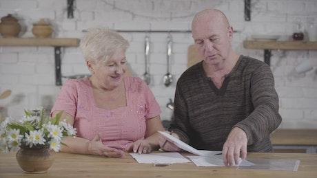 Elderly couple discuss bills in kitchen