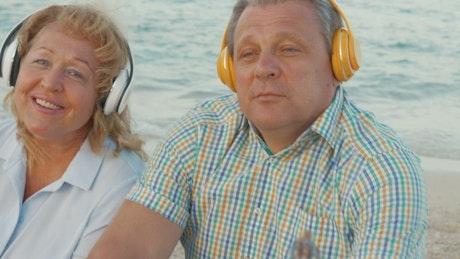 Elderly couple enjoying music at the beach