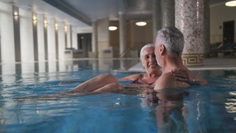 Elderly couple enjoying time in the pool