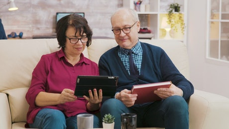 Elderly couple enjoying video call on sofa with tablet