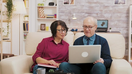 Elderly couple on sofa with laptop shopping online