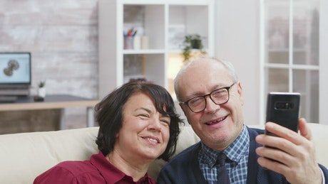 Elderly couple taking a photo together at home