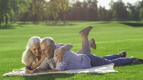 Elderly couple using a phone outside
