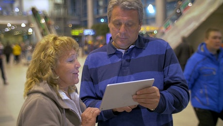 Elderly couple using a tablet while out in town