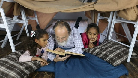 Elderly man reading a book to children