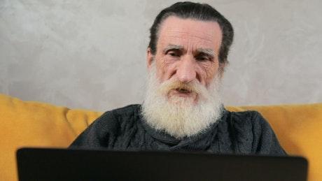 Elderly man stressed over broken laptop