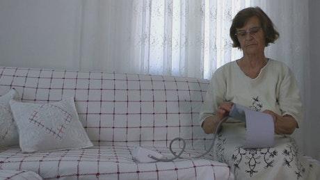 Elderly woman checking her blood pressure