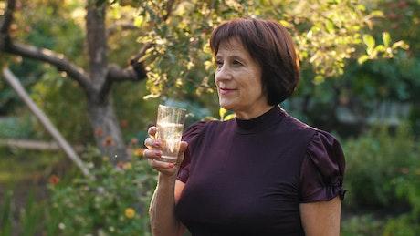 Elderly woman drinking water in her home garden
