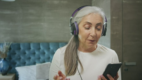 Elderly woman enjoys music app with headphones