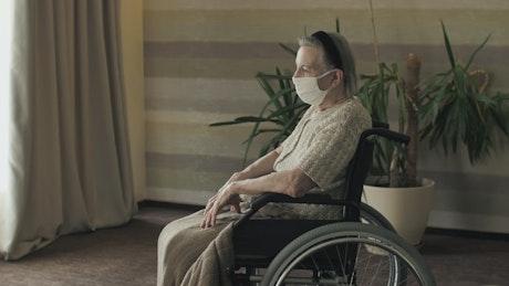 Elderly woman in a wheelchair wearing mask