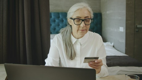 Elderly woman online shopping uses credit card payment