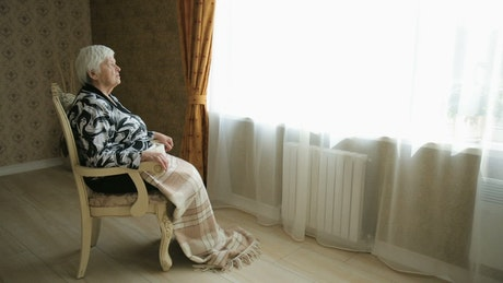 Elderly woman sitting in front of the window