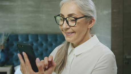 Elderly woman smiles while using mobile app