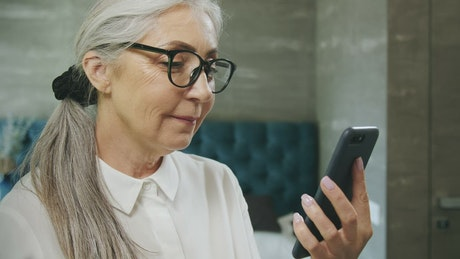 Elderly woman texts on mobile phone and smiles