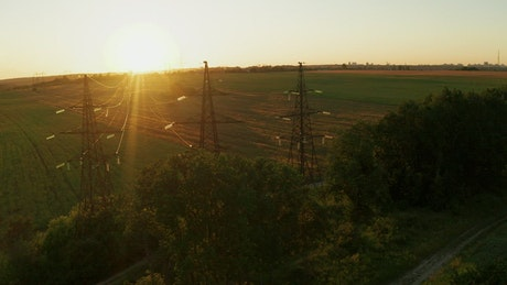 Electric power lines in the field at sunset