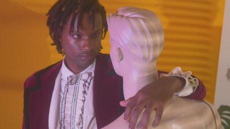 Elegant man hugging and staring at a mannequin