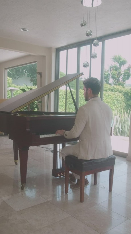 Elegant man playing the piano in a lobby