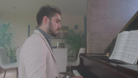 Elegant man playing the piano in a luxurious home