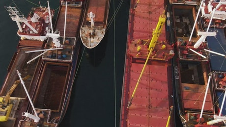 Empty cargo ships lined up on a coast from the air