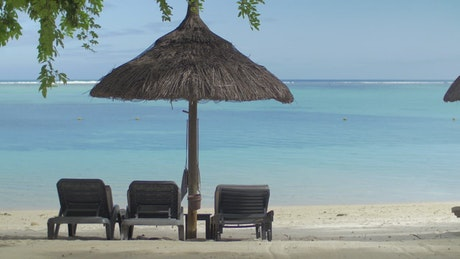 Empty wooden chairs on a tropical beach