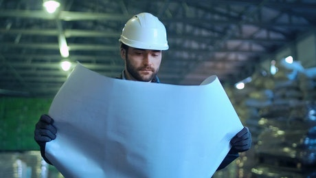 Engineer holding a blueprint in a warehouse