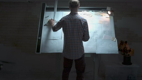Engineer looking over plans on a board