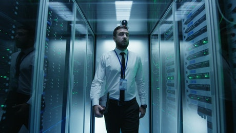 Engineer walking among server racks
