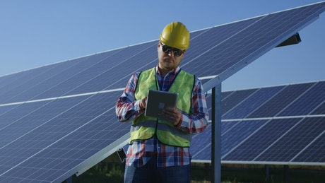 Engineer with a tablet in the solar panels field