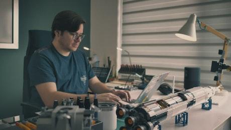 Engineer working on his computers in his workshop