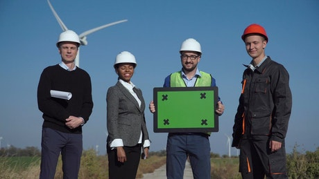 Engineers on a wind farm holding a green screen
