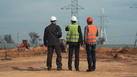 Engineers talking in front of the electrical towers