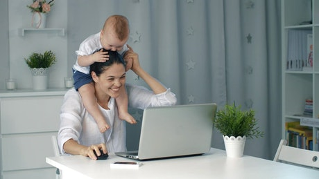 Enterprising mom plays with her baby while working