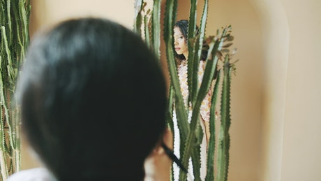 Ethnic fashion model poses with cactus