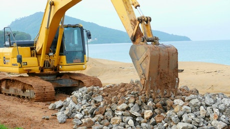 Excavator moving rocks