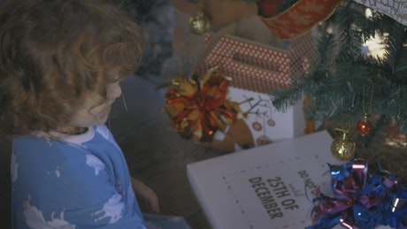 Excited girl opening gifts on Christmas morning