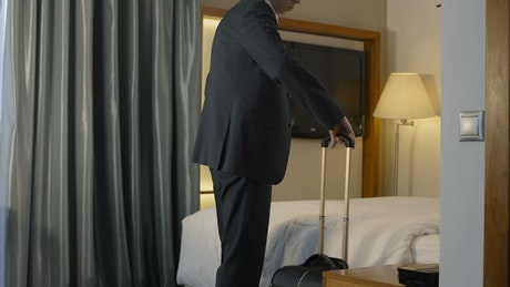 Exhausted businessman arriving to the hotel room