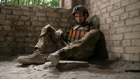 Exhausted soldier after a battle in a war zone