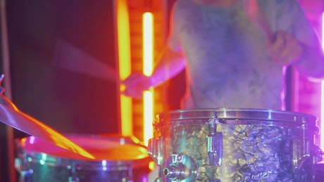 Experienced drummer performing on stage with lights