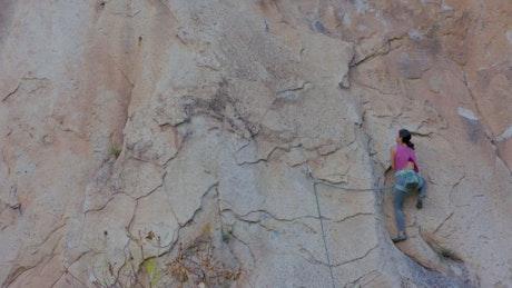 Experienced female mountaineer climbing a vertical mountain