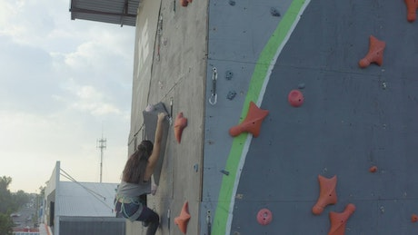 Experienced female mountaineer climbing on top of a wall