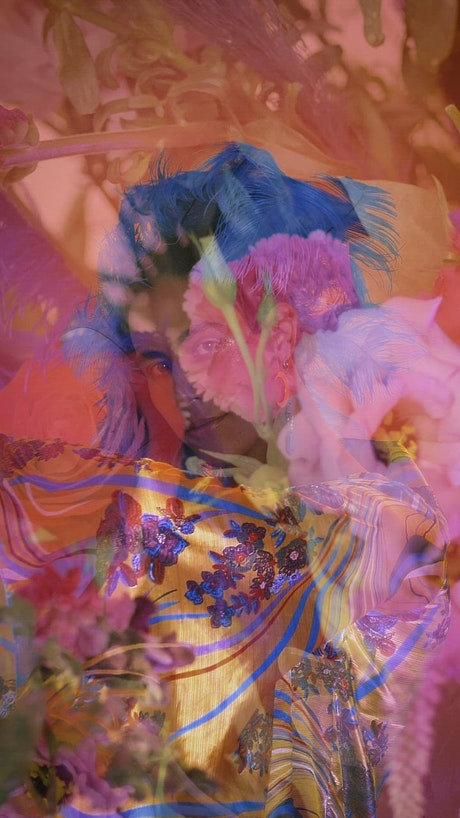 Extravagant gay boy in abstract video with flowers