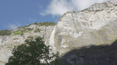 Extreme parachutists falling from a crag