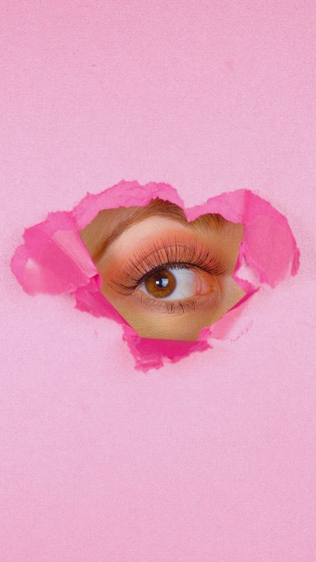 Eye of a woman peeking out of the hole of a pink paper screen