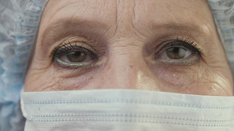 Eyes of an old female doctor wearing mask
