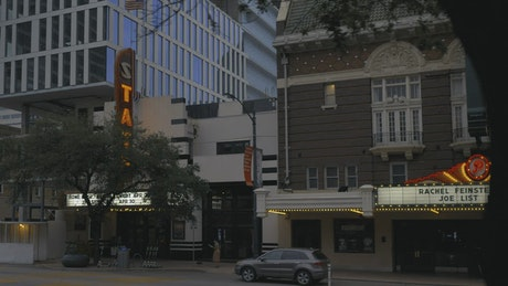 Facade of a theater with a sign and a luminous marquee