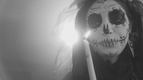 Face of a catrina with a candle, black and white