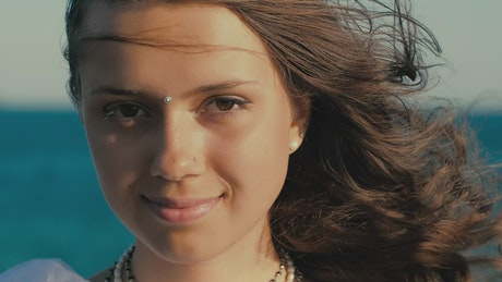 Face of a cheerful girl with watching near the sea